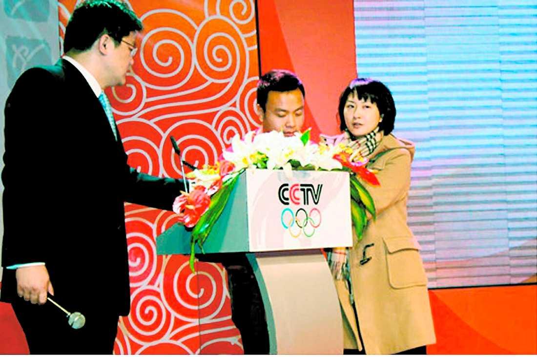 HÄMND I RUTAN Kinesiska stats-tv:n inviger sin OS-kanal. Zhang Bin (till vänster)får äran att vara programledare för premiärsändningen. Plötsligt rusar hans fru, som också är känd programledare i kinesisk tv, fram till talarstolen och avslöjar att hennes man varit otrogen. Hon hinner säga mycket innan hon motas ut.