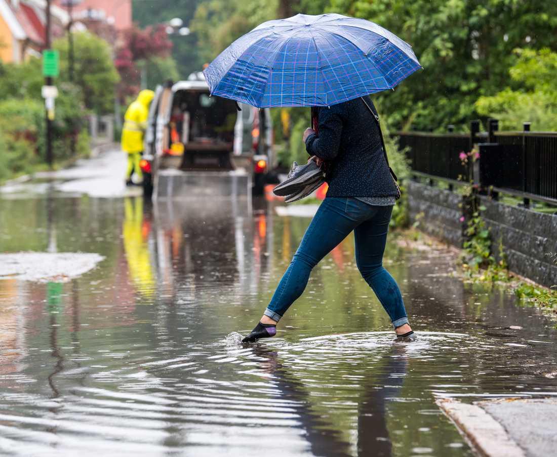 I Enskede i Stockholm vräkte regnet ner och en kvinna tvingades ta av sig skorna och vada fram.