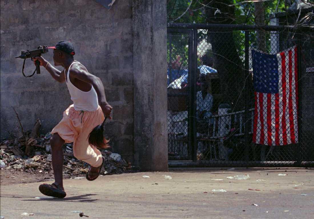 En rebell i Ulimo-gerillan i Liberia skjuter mot sina motståndare utanför en amerikansk beskickningsbyggnad 1996.