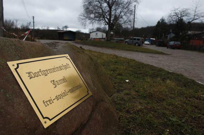 """En mässingskylt med inskriptionen """"Village Community Jamel free-social-national"""" är fäst på en sten vid vägen. Fler än hälften av husen bebos av nynazister."""