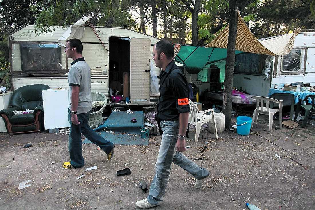 Tömmer lägren I går skickade Frankrike 93 romer till Rumänien. Två civilpoliser kontrollerar ett romerläger.