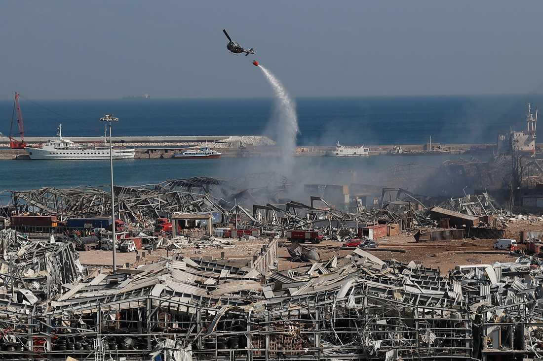 En arméhelikopter dumpar vatten över den pyrande bråten vid skådeplatsen för tisdagens explosion. Över 100 människor har dött och tusentals har skadats.