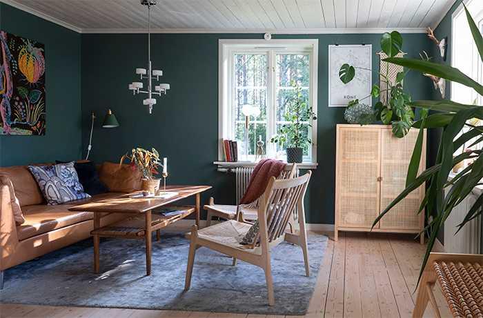 Den skogsgröna tonen är en fin fond mot skogen utanför fönstren. Soffa och rottingskåpet kommer från Ikea. Bordet är ett blocketfynd, liksom taklampan. Mattan kommer från Åhléns och fåtöljen från Jotex.