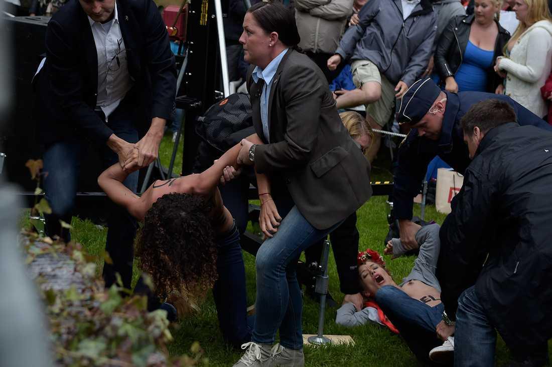 Femen-aktivister brottas ner av polis.