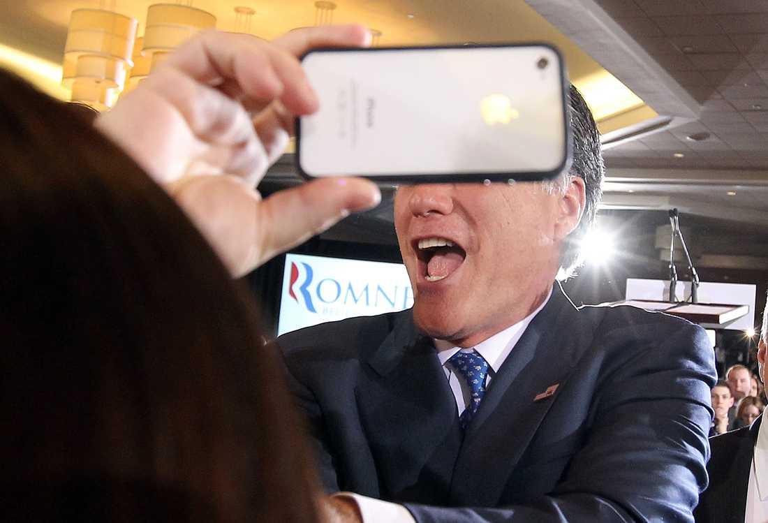 Mitt Romney spexar med en mobiltelefon.