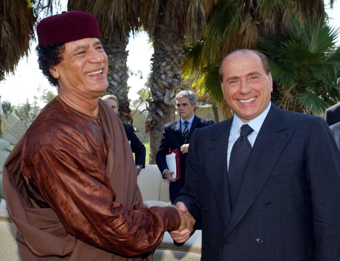 Muammar Gaddafi har länge varit vän med Italiens premiärminister Silvio Berlusconi. Här skakar de hand i Tripoli 2002.