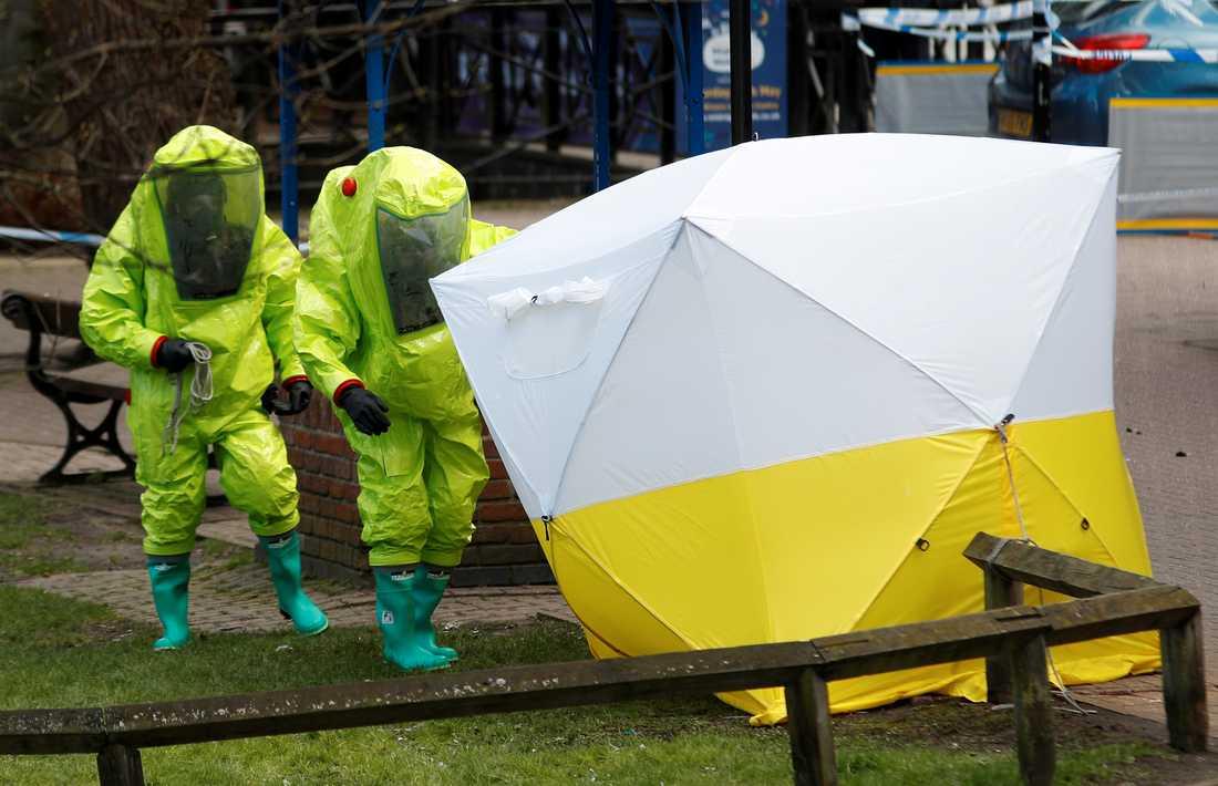 Myndighetspersonal i skyddsdräkter undersöker parkbänken där Sergei och Yulia hittades.