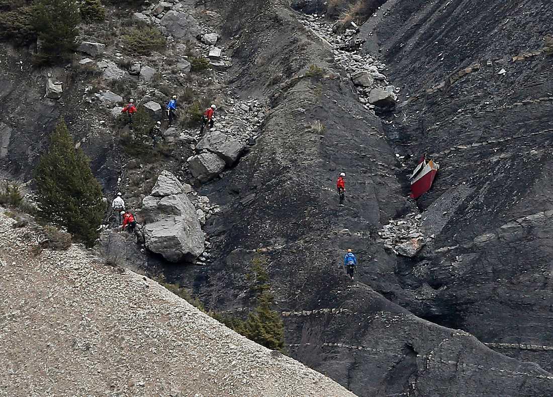 Räddningspersonal bland spillrorna efter det kraschade planet.