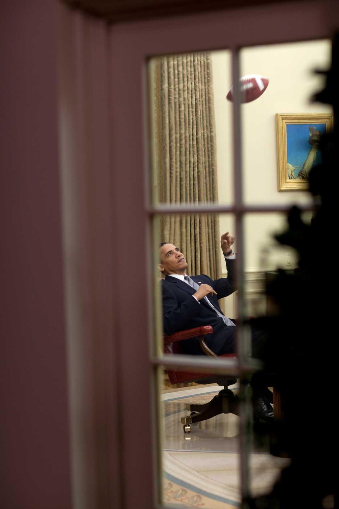 Obama leker med en amerikansk fotboll på sitt kontor.