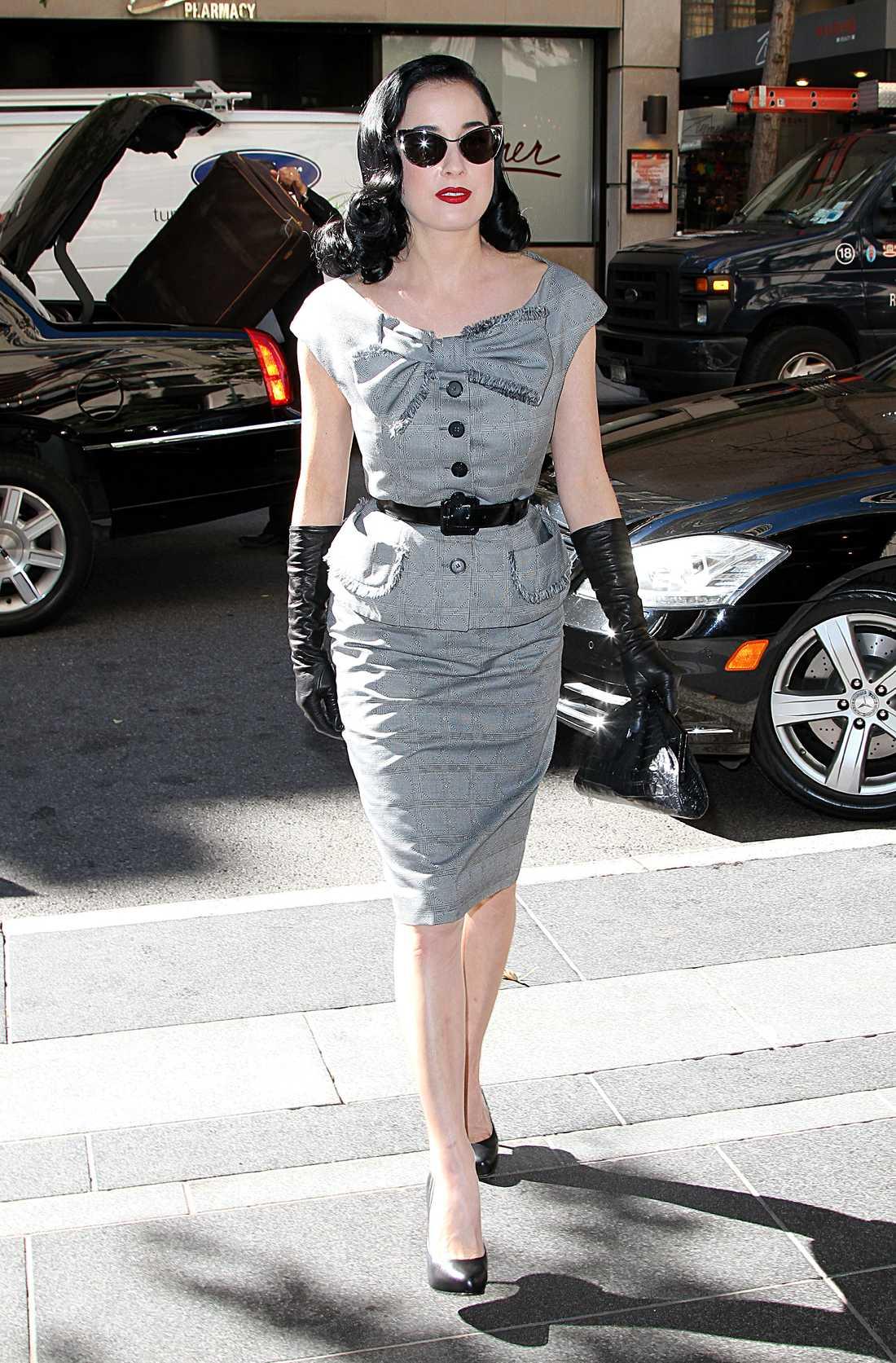 Dita von Teese är Hollywoodglammig i grå dräkt med skinnhandskar och höga pumps.