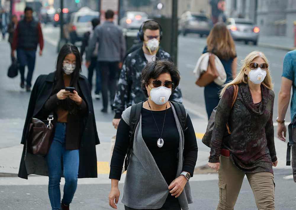 Människor utrustade med andningsmasker i ett rökfyllt San Fransisco.