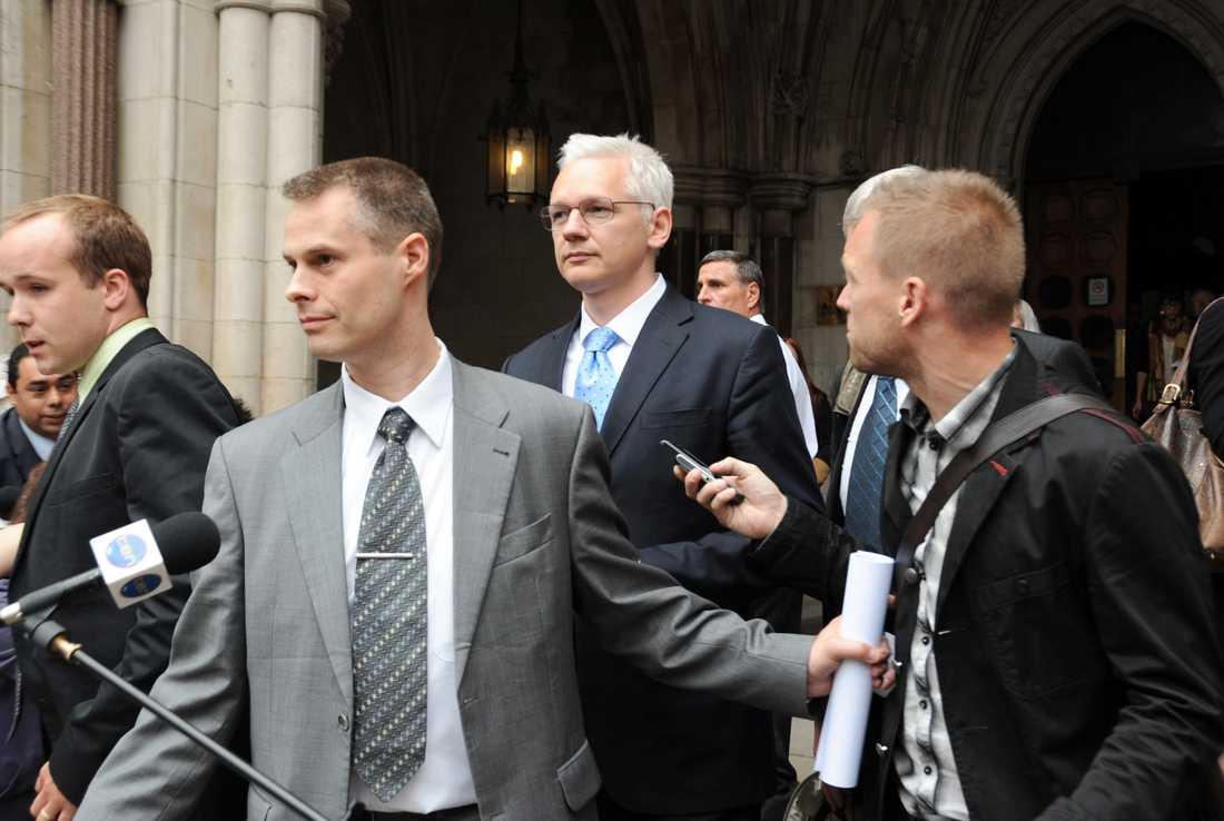 Julian Assange på väg ut ur rätten efter förhandlingarnas första dag. Till höger Aftonbladets Torbjörn Ek.