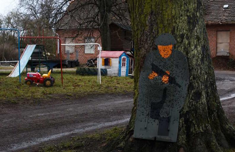 En bild av en soldat fylld med hål står bredvid en lekpark.