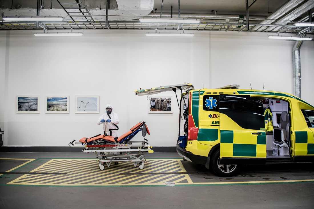 Jonas Östberg står i vita skyddskläder, lila handskar och skyddsmask. Han sanerar en ambulans som precis lämnat av en patient.