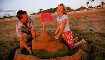 """Pelle Svensson med dottern Erika prövar hållfastheten hos ett marockanskt sandslott, naturligtvis utrustat med flagga. """"Ren och fin strand, inte en sten"""", säger Pelle Svensson."""