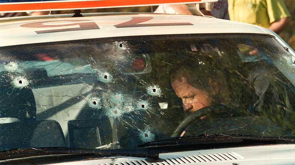 SKÖT RÄTT MOT POLISBILEN Polisens tekniker undersöker polisbilen där skotten gått rätt igenom vindrutan efter rånet mot Östgötabanken i Kisa 28 maj 1999.