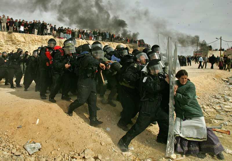 En modern klassiker. Bilden föreställer en ensam judisk kvinna som försöker stoppa israeliska säkerhetsstyrkor från att ta sig in i, och utrymma, de illegala judiska bosättningarna på Västbanken år 2006.För den här bilden fick footgrafen Oded Balialty Pulitzerpriset.