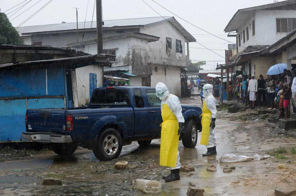 Sjukvårdare på väg att hämta en död kropp som hittats i Monrovia.
