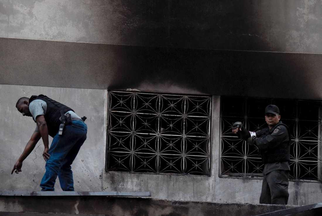 Säkerhetsvakter kontrollerar byggnad efter explosion under president Maduros tal i Caracas.