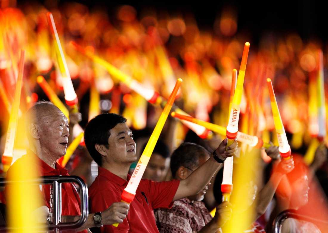 Singapores före detta premiärminister Lee Kuan Yew viftar med en ljusstav under firandet av Singapores nationaldag på fredagen.