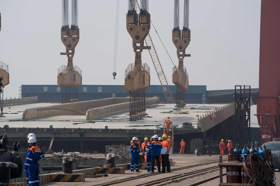 Den stora brokonstruktionen lyfts till pontonerna i hamnen i den kinesiska staden Zhongshan för att sedan avgå mot Stockholm.