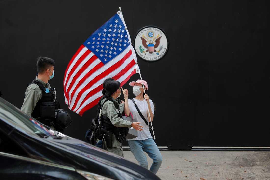 En aktivist med en amerikansk flagga motas bort av polis vid en manifestation utanför USA:s konsultat i Hongkong den 4 juli.