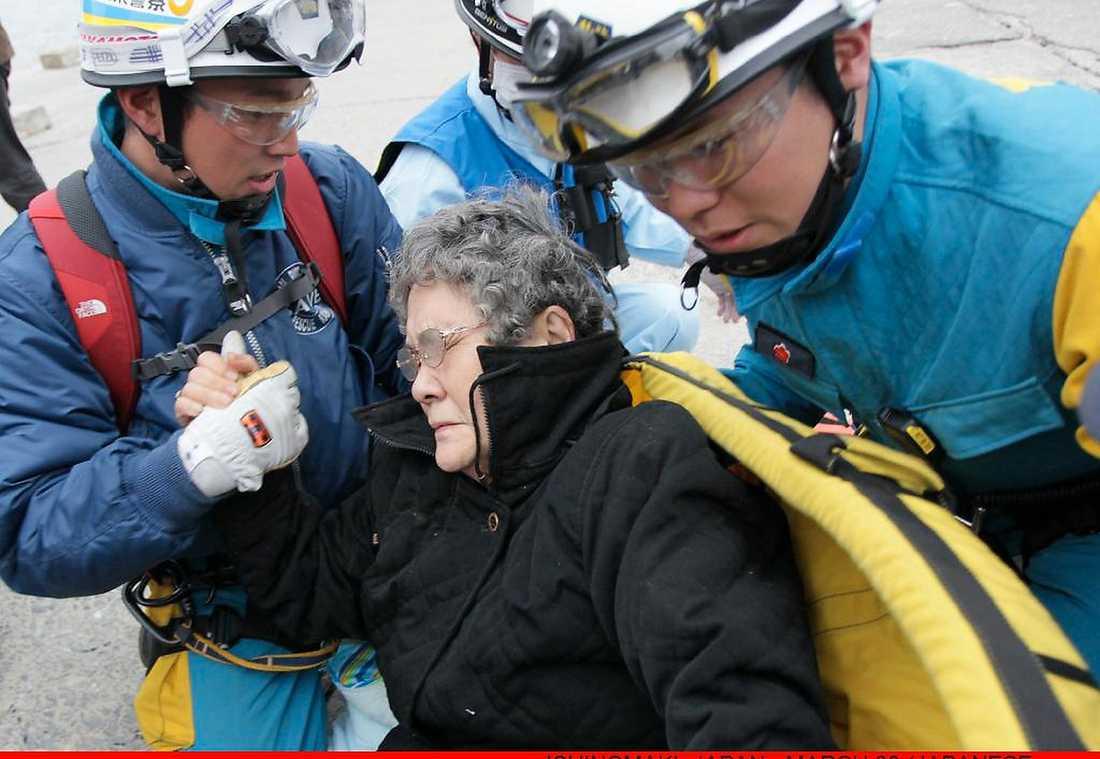 """räddad – efter nio dygn Sumi Abe, 80, tas om hand av räddningsarbetare efter att ha räddats ur rasmassorna efter nio dygn. På frågan om hon var skadad svarade hon """"Nej""""."""