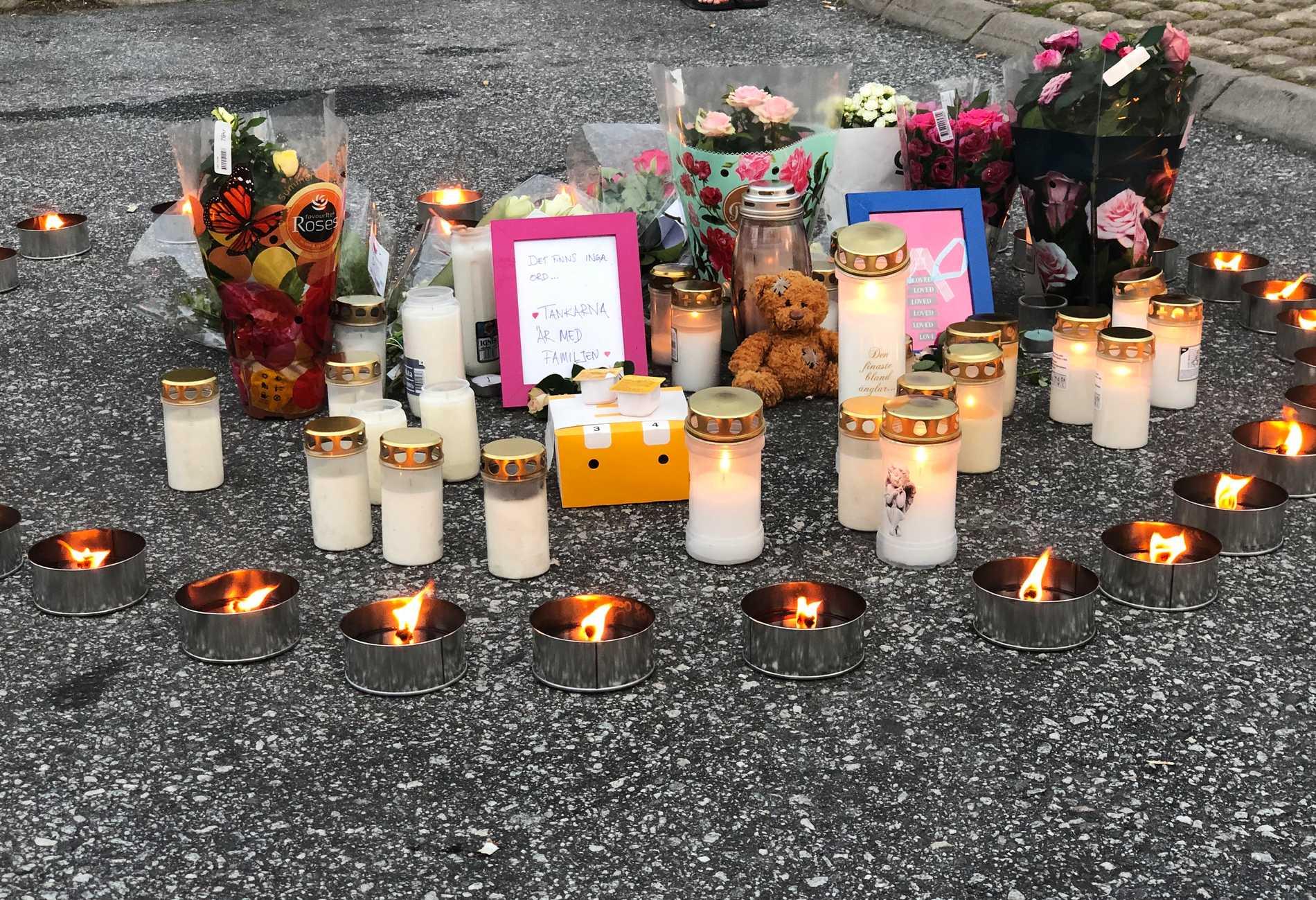 Flera personer har lagt blommor och ljus på platsen där den 12-åriga flickan sköts.
