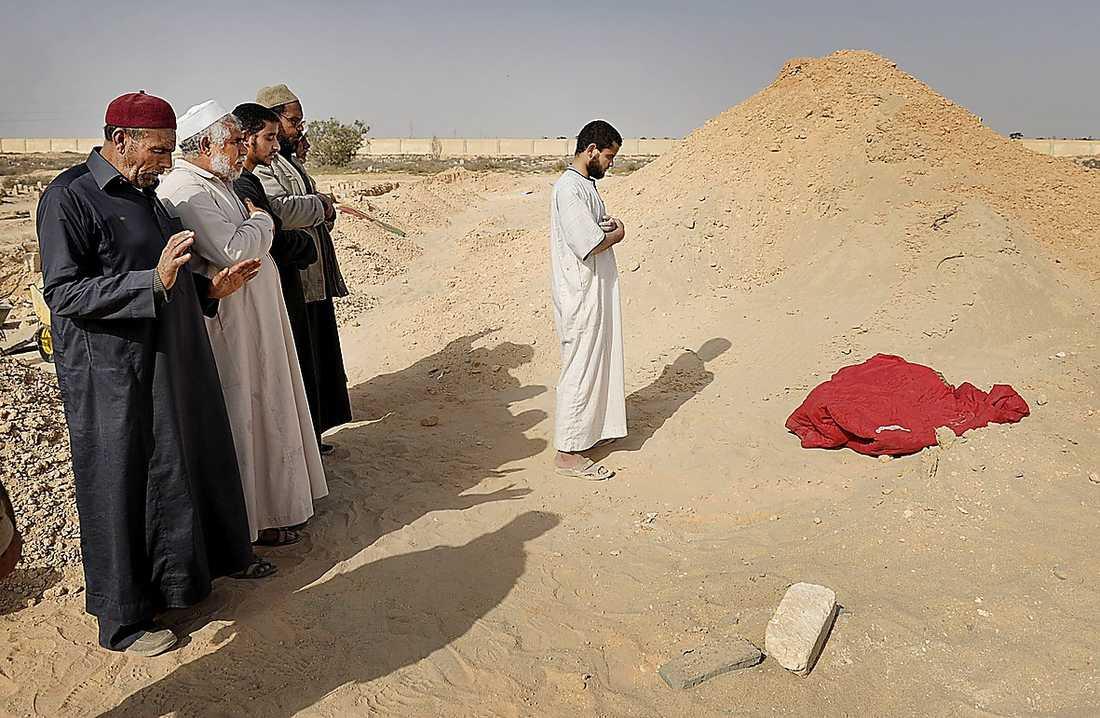 En grupp män begraver en släkting under böner utanför staden.