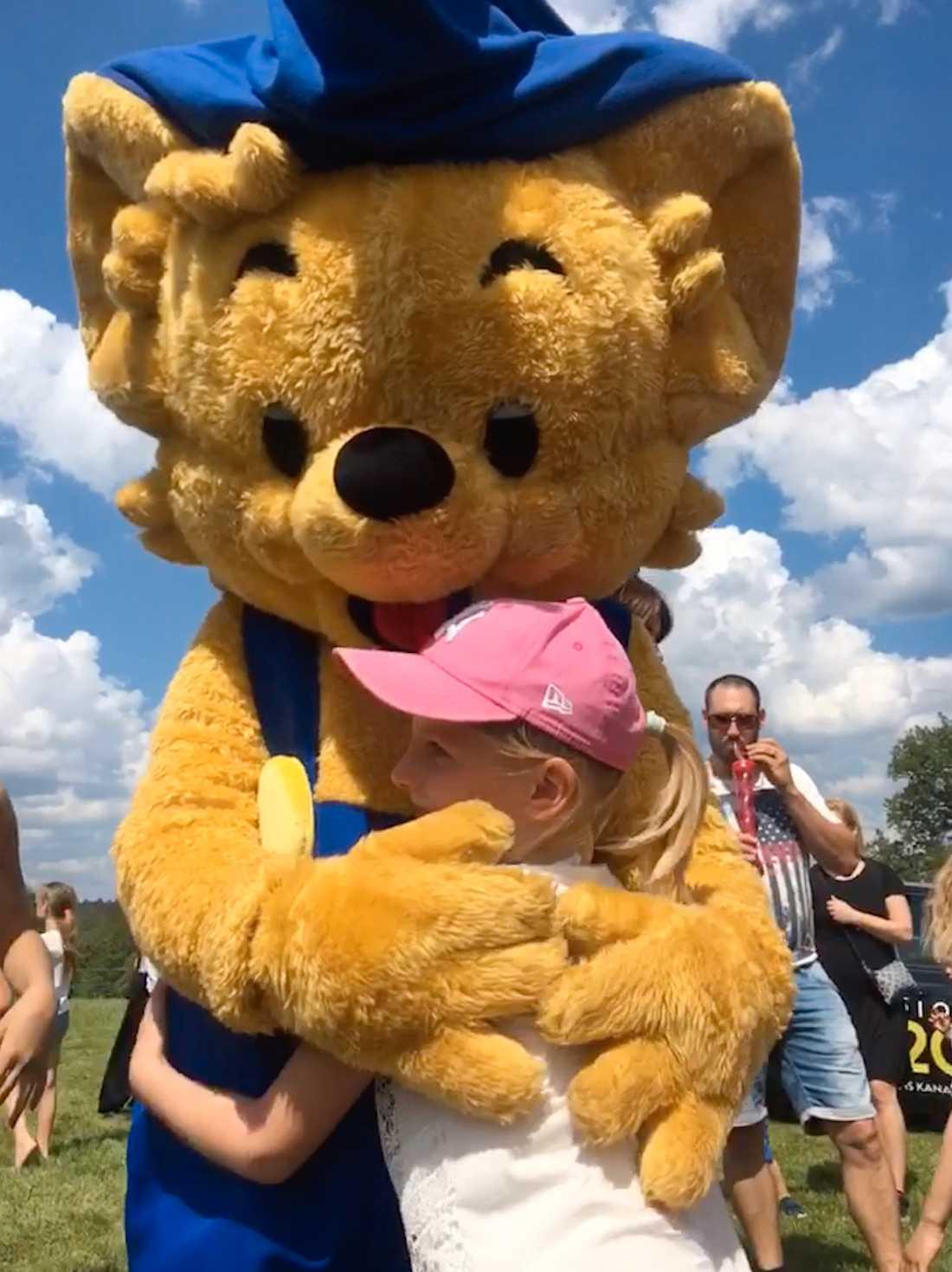 Freja, 6, får en luden kram av Bamse på Barnens dag i Floda.