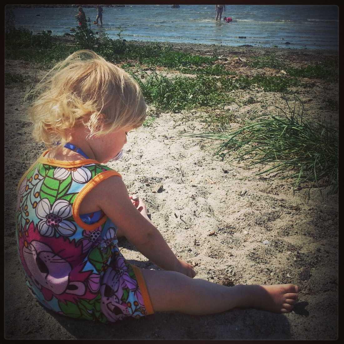 Min dotter Milla leker på stranden.