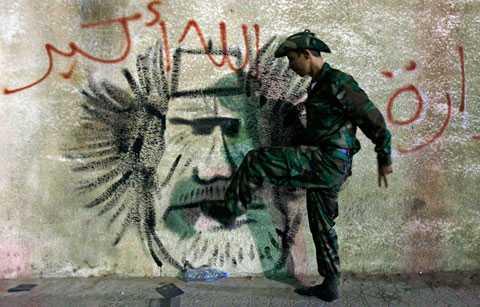 En före detta libysk rebell sparkar på en teckning av Muammar Gaddafi vid gränsen mellan Tunisien och Libyen.