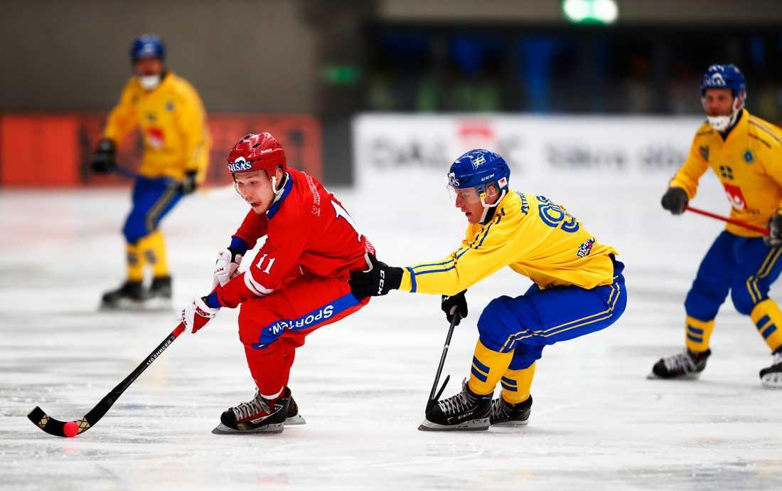 Erik Pettersson försöker stoppa ryske Vadim Chernov i bandy-VM:s premiärmatch i Vänersborg. Sverige vann med 6–4 mot Ryssland.