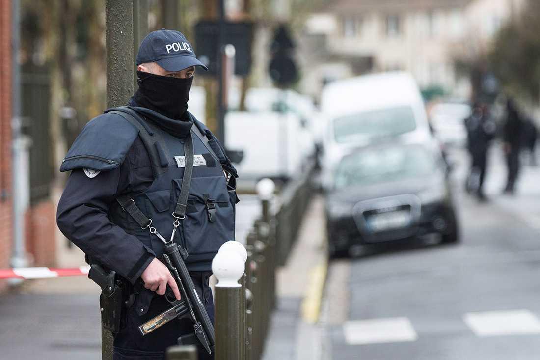 En polis står utanför en byggnad under ett terrorinslag i Argentuill nära Paris 25 mars.