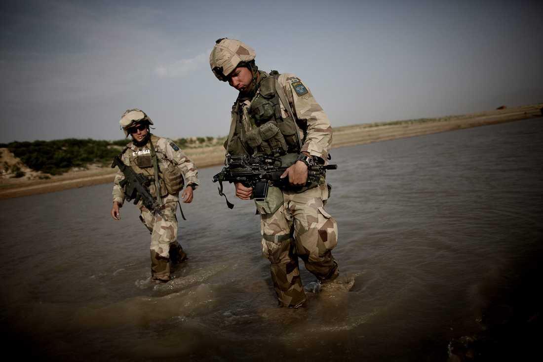 Två svenska soldater vadar över floden Balkh för att hitta en plats där stridsfordon kan korsa.