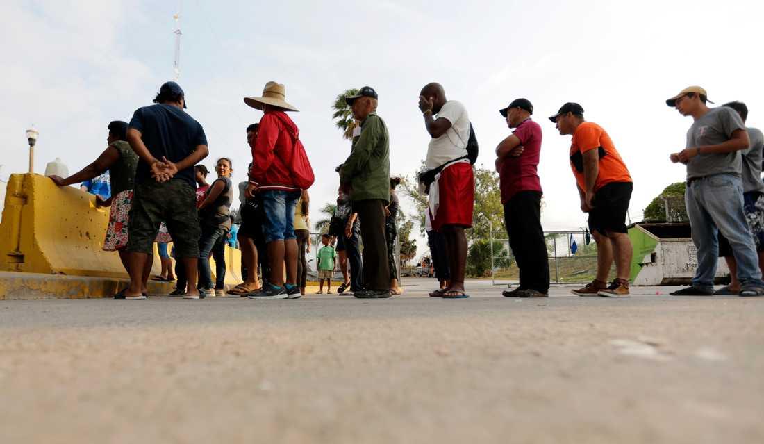Migranter som söker asyl i USA köar för att få ett mål mat som delas ut av volontärer i Matamoros i Mexiko, nära gränsen till USA. Bilden är från den 29 april 2019.