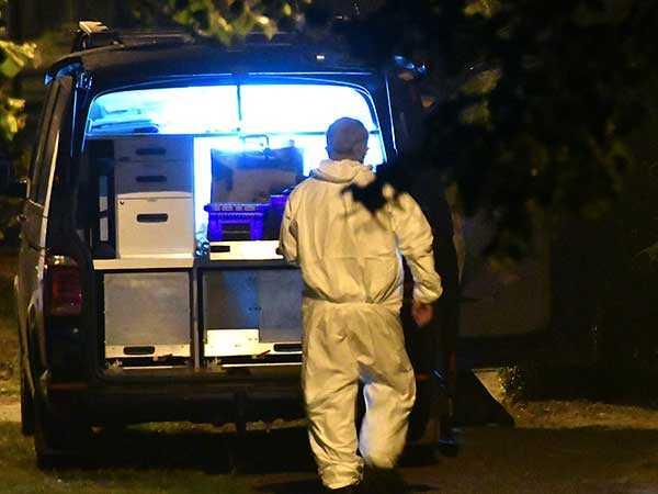 Kriminaltekniker undersöker bostaden i Trelleborg där två personer hittades döda.
