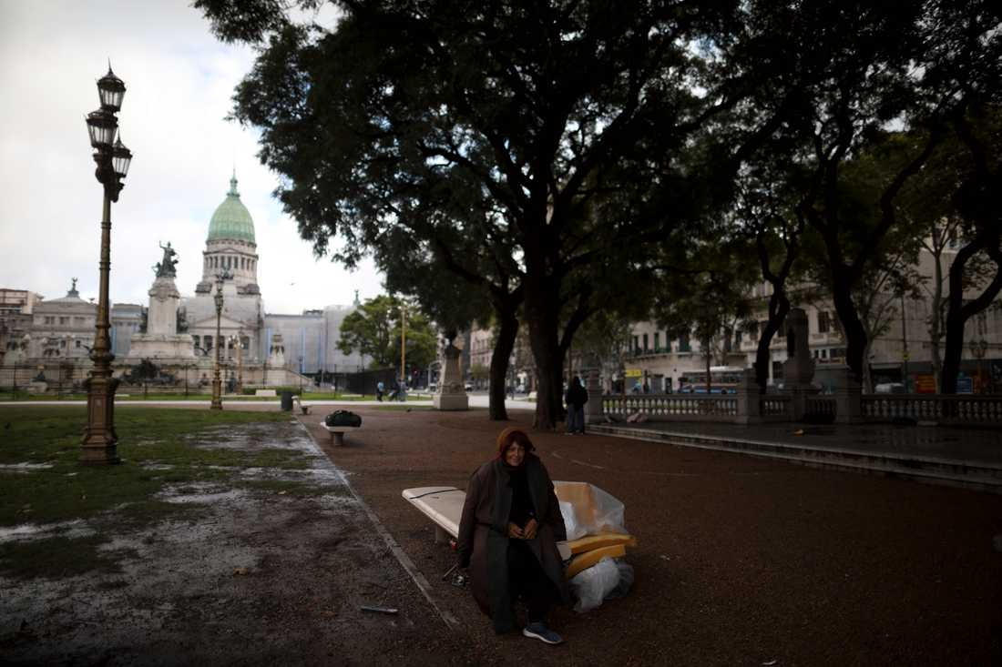 En kvinna sitter på en bänk utanför kongressen i Buenos Aires, Argentina. Få människor syns ute i huvudstaden då karantän införts.