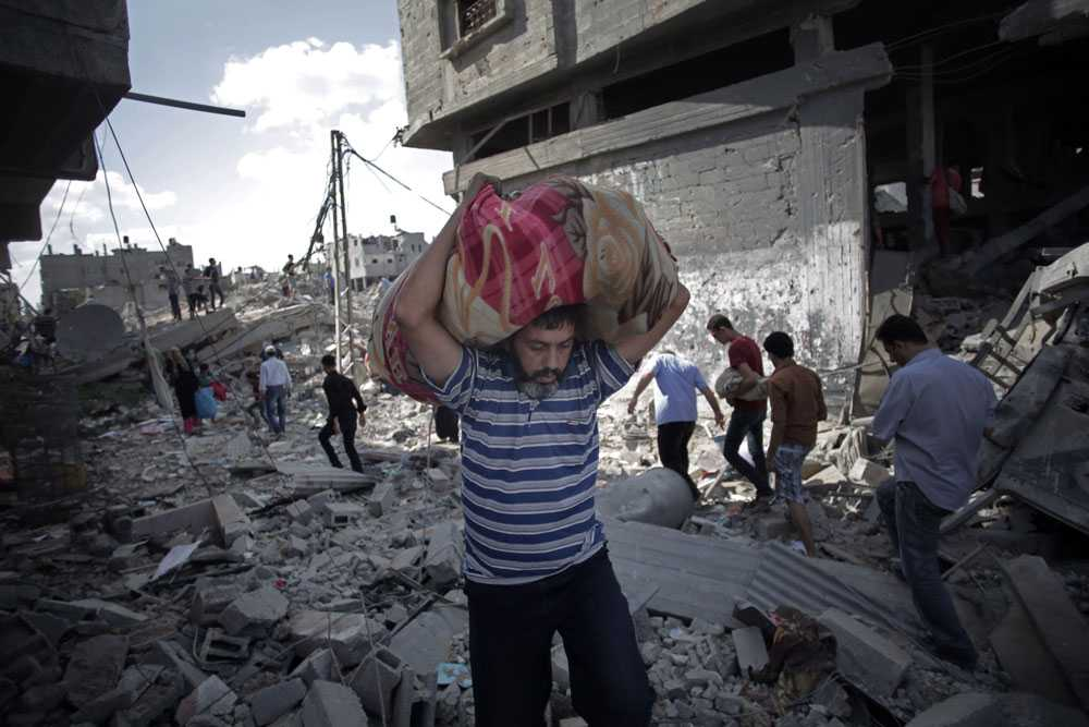 En man försöker samla ihop några av sina ägodelar efter bombningarna.