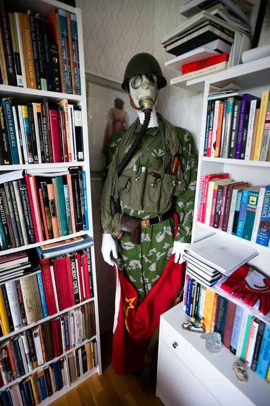 I vardagsrummet står en docka i mänsklig storlek, iförd sovjetisk stridsuniform från 1970-talet och gasmask.