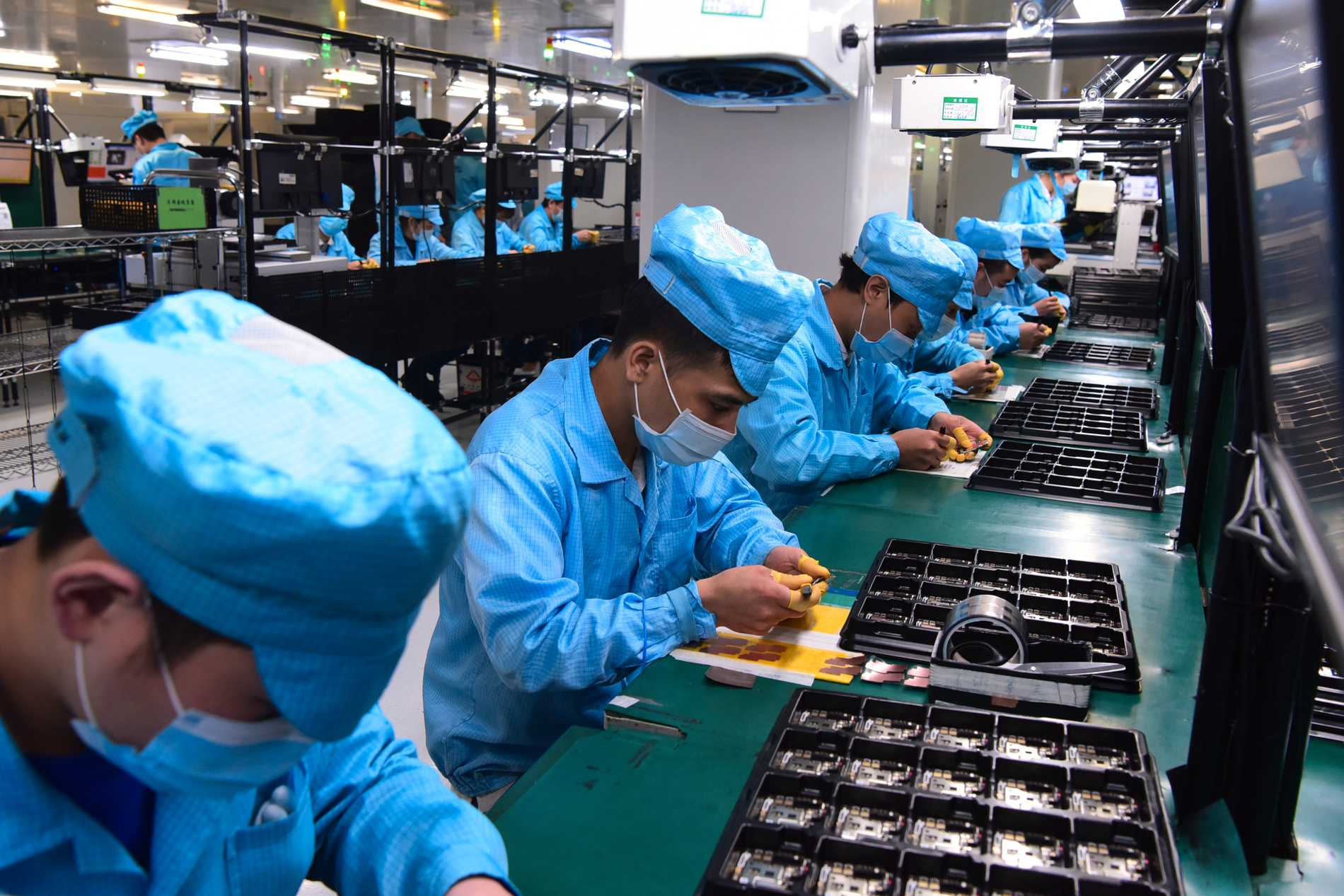 Anställda på en telekomfabrik i Dongguan med munskydd. Bilden är från förra året – nu inleder industristaden masstestning.