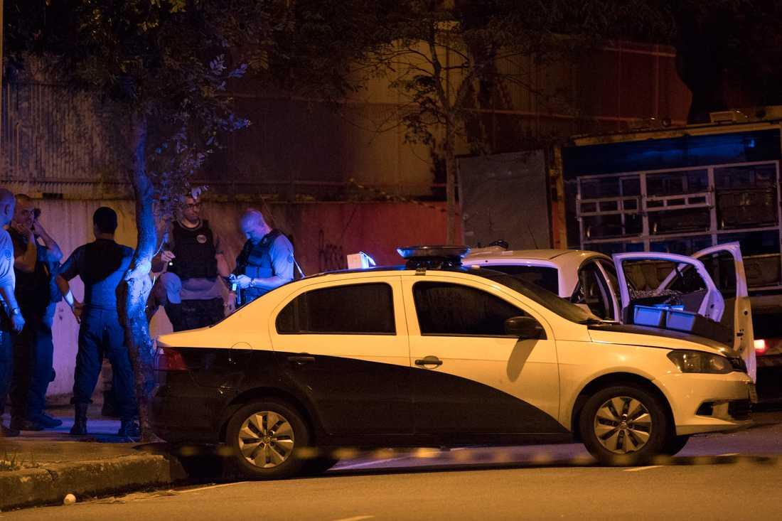 Poliser undersöker brottsplatsen och bilen där Marielle Franco och hennes chaufför mördades i Rio de Janeiro den 14 mars 2018.