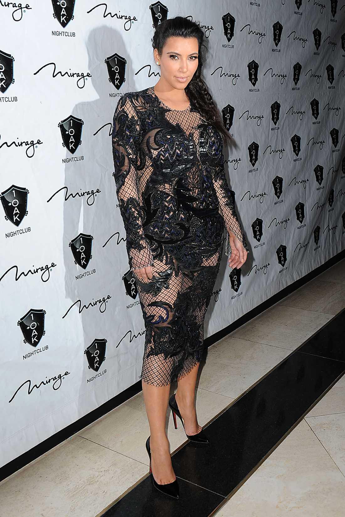 Gravida Kim Kardashian i vågat, svart fodral, Louboutins på fötterna och slarviga flätor i håret.