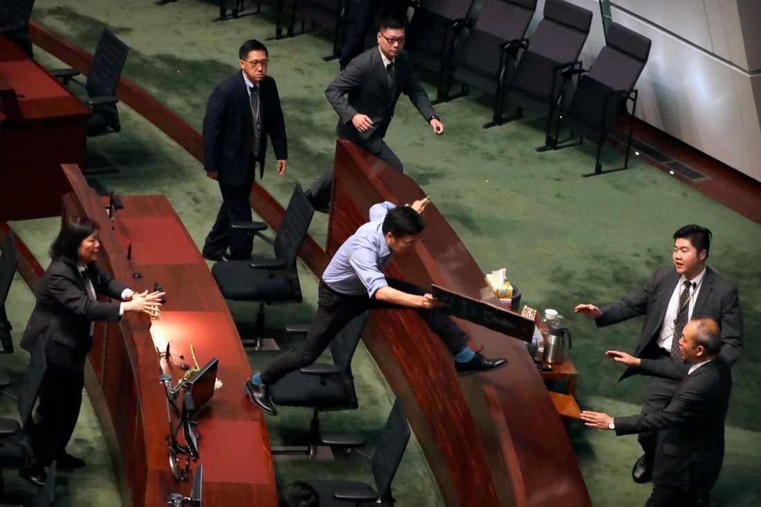 Vakter försöker få tag i ledamoten Au Nok-Hin som protesterade i parlamentet i Hongkong.