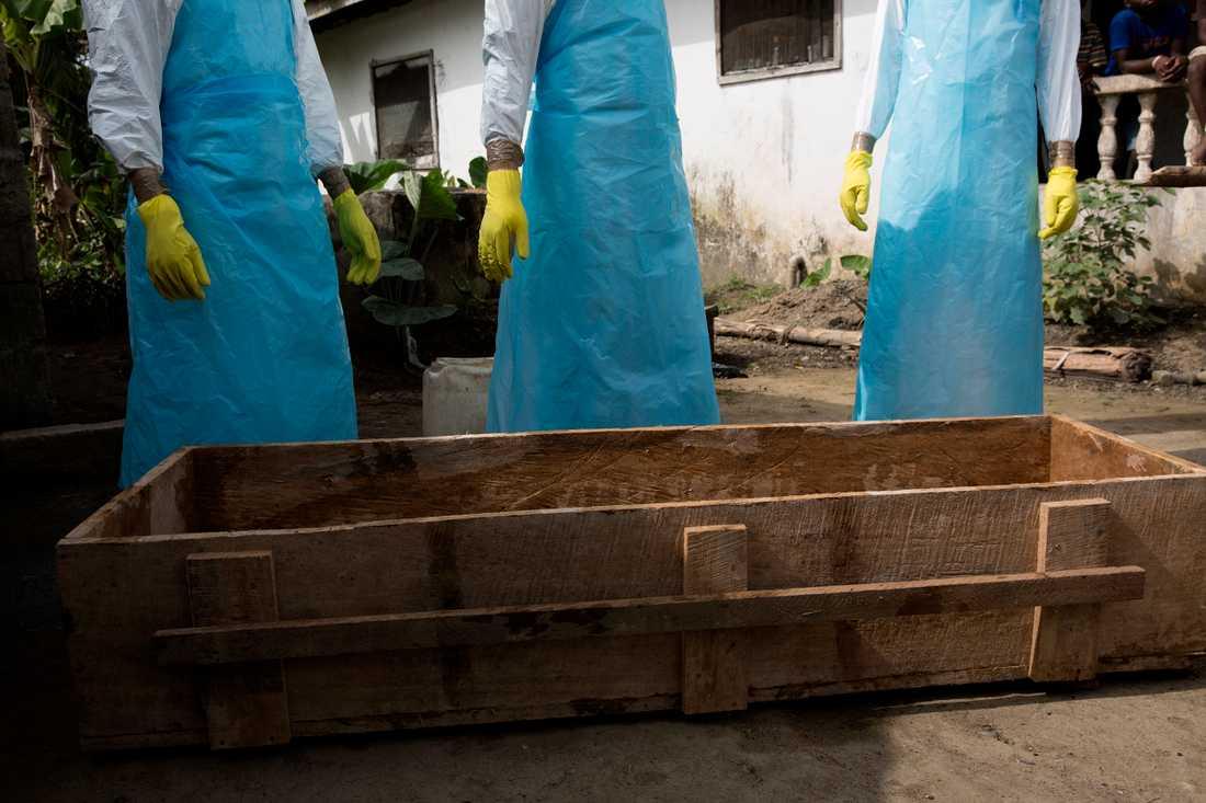 Röda korsets begravningsteam består av unga män och kvinnor. för 80 dollar i månaden gör de jobbet ingen annan vill göra. de hämtar de misstänkta ebolafallen. de bär skyddsdräkt, dubbla handskar, andningsskydd, skyddsglasögon och stövlar.  Jag är inte rädd, säger thomas freeman, 25.