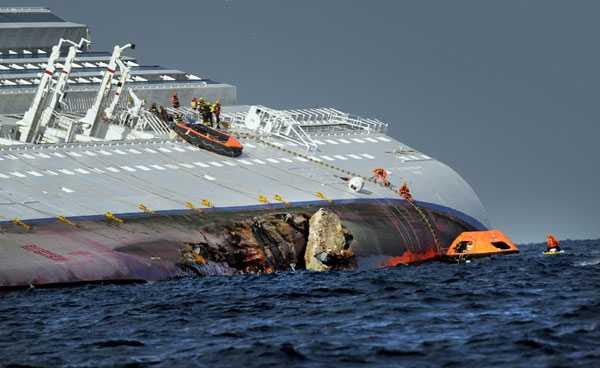 Räddningsarbetarna letade febrilt efter överlevande i och kring fartyget. Här på bilden syns det stora hål som revs upp när kryssningsfartyget gick på grund.