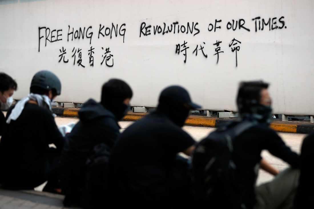 Demonstranter vid en vägg som sprejats med slagord.