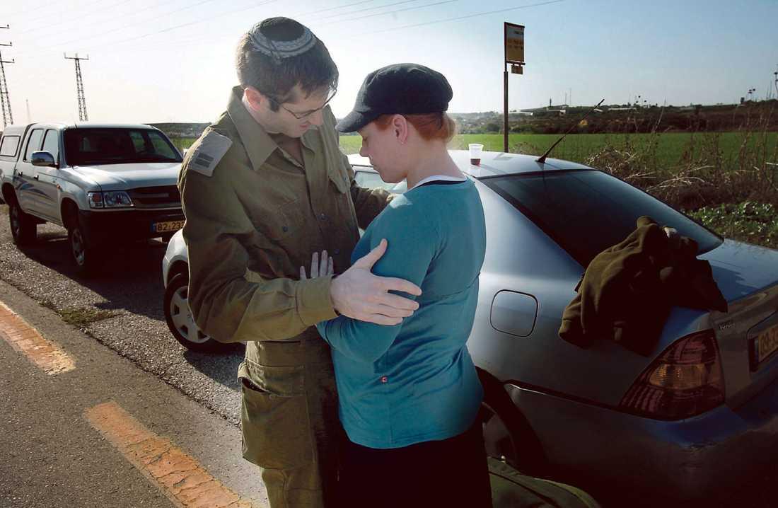 """advokat blir soldat Klockan ett på natten väcktes Asaf, 30, och gravida hustrun Lindy, 27, av telefonsamtalet där Asaf beordrades att inställa sig med omedelbar verkan. Lindy gråter oavbrutet när de tar farväl. """"Jag vet inte om jag kommer hem"""", säger Asaf."""
