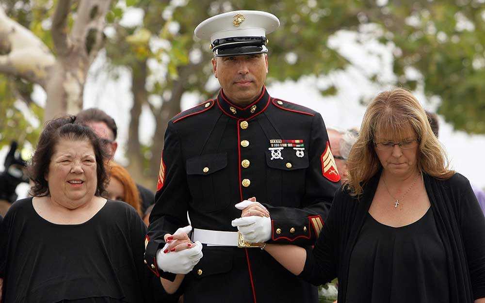 Robert Acosta (mitten) leder sin mamma Dianna Bedwell (till vänster) och sin syster Debbie Apple under begravningen av deras far.
