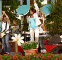 Carola springer in på scenen och hoppar direkt upp på en blomkruka.